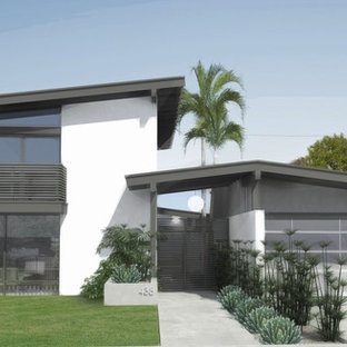 Mid-sized mid-century modern white two-story stucco exterior home photo in Los Angeles with a hip roof