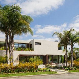 Diseño de fachada blanca, marinera, de tamaño medio, de tres plantas, con revestimiento de estuco y tejado plano