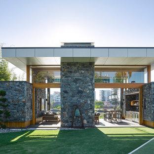 Foto de fachada gris, minimalista, de tamaño medio, de una planta, con revestimiento de piedra y tejado plano