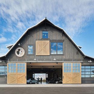 Ejemplo de fachada marrón, de estilo de casa de campo, grande, de dos plantas, con revestimiento de madera, tejado a doble faldón y tejado de metal