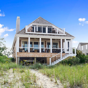 Beach style brown two-story wood exterior home idea in New York with a hip roof