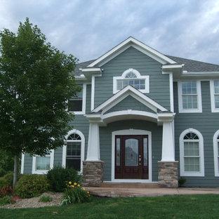 Cette photo montre une façade de maison verte chic de taille moyenne et à un étage avec un revêtement en panneau de béton fibré et un toit à quatre pans.