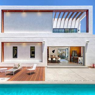 Diseño de fachada blanca, minimalista, grande, de dos plantas, con tejado plano y revestimiento de estuco