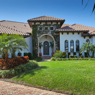 Inspiration for a large mediterranean white two-story stucco gable roof remodel in Miami