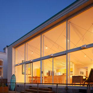 Foto de fachada gris, costera, de una planta, con revestimiento de vidrio y tejado plano