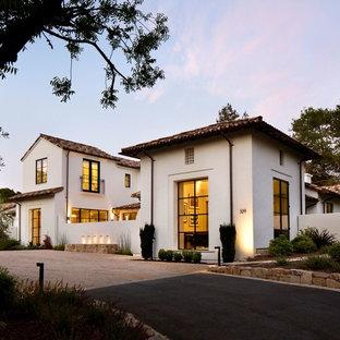Foto de fachada blanca, minimalista, grande, de dos plantas, con revestimiento de estuco y tejado a dos aguas