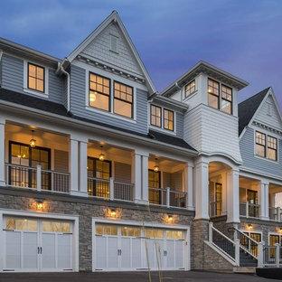Foto de fachada gris, marinera, grande, a niveles, con tejado a dos aguas y revestimientos combinados