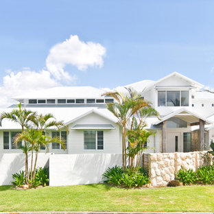 Beach style two-storey white house exterior in Gold Coast - Tweed with a gable roof.