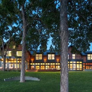 Aménagement d'une très grand façade en brique rouge rétro à un étage avec un toit à deux pans.