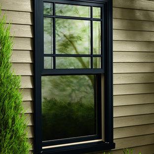 Ejemplo de fachada verde, de estilo de casa de campo, con revestimiento de madera