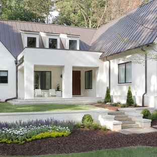 Example of a transitional white two-story brick gable roof design in Atlanta with a metal roof