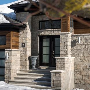 Ejemplo de fachada beige, tradicional, de tamaño medio, de una planta, con revestimientos combinados y tejado a doble faldón