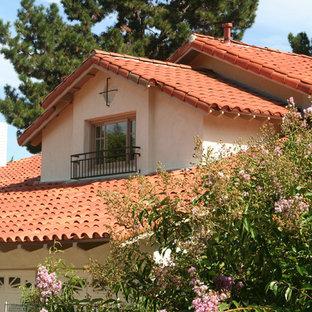 Modelo de fachada beige, mediterránea, de tamaño medio, de dos plantas, con revestimiento de vidrio y tejado a dos aguas