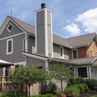 Ejemplo de fachada gris, ecléctica, de tamaño medio, de dos plantas, con revestimiento de vinilo