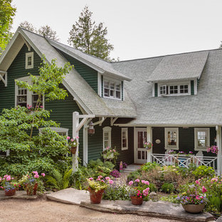 Large cottage chic green two-story wood exterior home photo in Milwaukee with a shingle roof