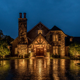 Huge mountain style brown two-story stone exterior home photo in Charlotte with a mixed material roof