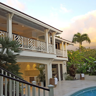 Inspiration for a mid-sized tropical white two-story vinyl exterior home remodel in Other with a hip roof