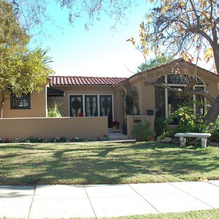 Example of an arts and crafts beige one-story stucco exterior home design in Los Angeles
