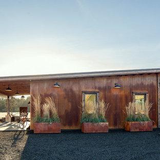 Ispirazione per la facciata di una casa unifamiliare piccola marrone industriale a un piano con rivestimento in metallo, tetto a una falda e copertura in metallo o lamiera