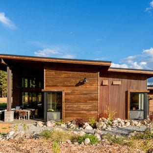 Foto della facciata di una casa unifamiliare marrone industriale a un piano di medie dimensioni con rivestimento in metallo, tetto a una falda e copertura in metallo o lamiera