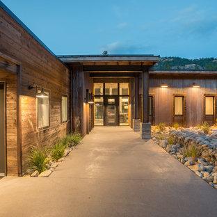 Неиссякаемый источник вдохновения для домашнего уюта: одноэтажный, коричневый частный загородный дом среднего размера в стиле лофт с облицовкой из металла, односкатной крышей и металлической крышей
