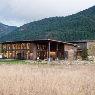 Cette image montre une façade de maison marron chalet de taille moyenne et de plain-pied avec un toit en appentis et un toit en métal.