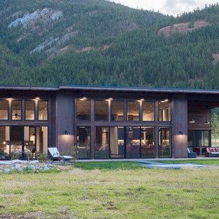 Ispirazione per la facciata di una casa unifamiliare marrone rustica a un piano di medie dimensioni con rivestimento in metallo, tetto a una falda e copertura in metallo o lamiera