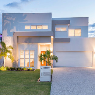 This is an example of a contemporary two-storey stucco white house exterior in Gold Coast - Tweed with a flat roof.
