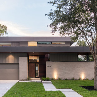 Inspiration for a mid-sized contemporary gray two-story brick flat roof remodel in Houston