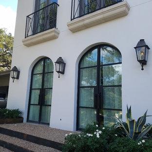 Modelo de fachada de casa blanca, mediterránea, grande, de dos plantas, con revestimiento de estuco, tejado a cuatro aguas y tejado de metal