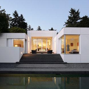 Inspiration för ett funkis vitt hus, med allt i ett plan och platt tak