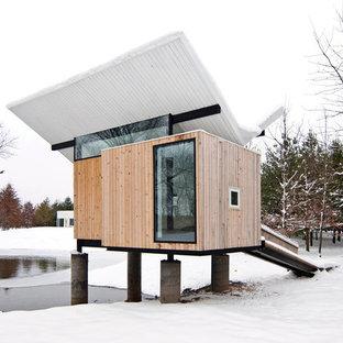 На фото: маленький, одноэтажный, деревянный, коричневый дом в современном стиле с крышей-бабочкой