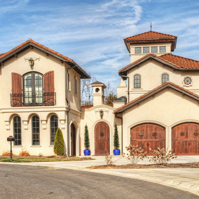 Example of a large tuscan beige three-story stucco gable roof design in Charlotte