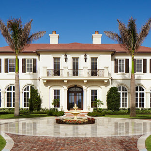 Example of a tuscan white two-story exterior home design in Miami with a hip roof