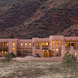 Foto della facciata di una casa unifamiliare ampia rosa american style a due piani con rivestimento in adobe e tetto piano