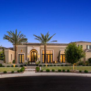 Example of a tuscan gray two-story stucco house exterior design in Phoenix with a hip roof and a tile roof
