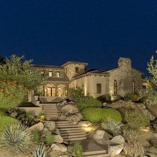 Mediterranean two-story stone exterior home idea in Phoenix