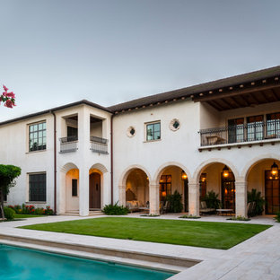 Example of a huge tuscan white two-story stucco house exterior design in Houston with a hip roof and a tile roof