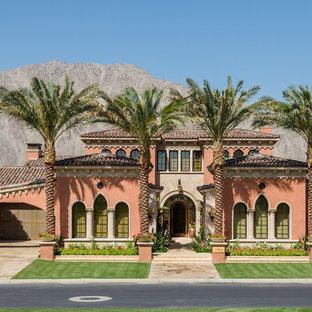 Idées déco pour une façade de maison rose méditerranéenne à un étage.