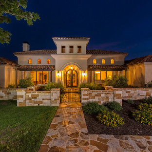 This is an example of a beige and large mediterranean two floor render house exterior in Austin with a hip roof.