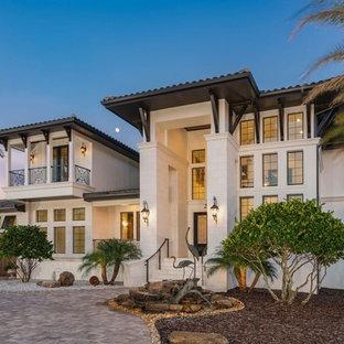 На фото: маленький, двухэтажный, белый частный загородный дом в средиземноморском стиле с облицовкой из цементной штукатурки, вальмовой крышей и металлической крышей