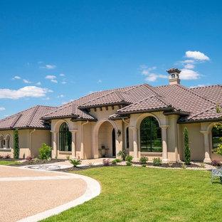 Diseño de fachada de casa beige, mediterránea, grande, de dos plantas, con tejado a cuatro aguas, tejado de teja de barro y revestimientos combinados