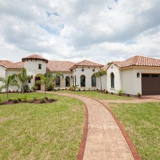 Large tuscan white one-story concrete exterior home photo in Austin with a tile roof
