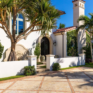 Huge mediterranean white two-story stone house exterior idea with a hip roof and a tile roof