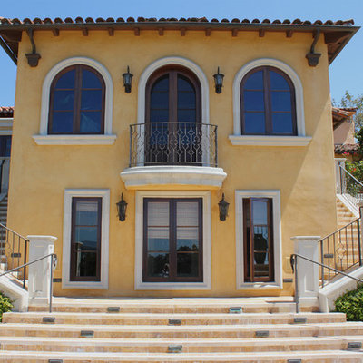 Inspiration for a large mediterranean yellow two-story house exterior remodel in Santa Barbara with a hip roof and a tile roof