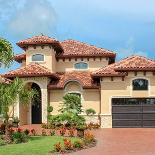 Example of a tuscan beige two-story exterior home design in Tampa