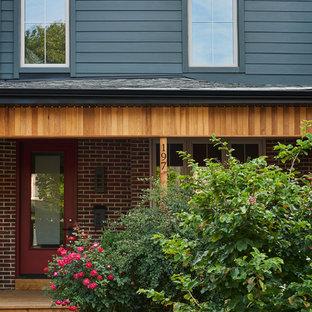 Foto de fachada de casa bifamiliar roja, bohemia, de tamaño medio, de dos plantas, con revestimiento de aglomerado de cemento, tejado a cuatro aguas y tejado de teja de madera