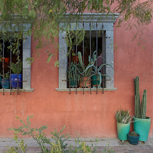 Inspiration for a southwestern red two-story stucco exterior home remodel in Other