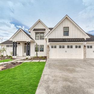 Cette image montre une grand façade de maison blanche rustique à un étage avec un revêtement mixte et un toit à deux pans.