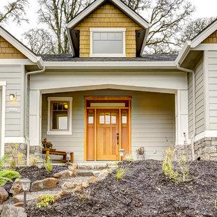 Diseño de fachada de casa amarilla, de estilo americano, grande, de dos plantas, con revestimientos combinados, tejado a dos aguas y tejado de teja de madera